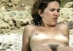 Happy naturist chick at a beach