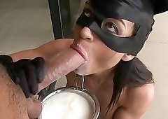 Brunette in a cat-woman mask sucking cock on camera