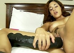 A brunette tests her sex toys by pushing them in her cunt