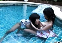 Buxom Thai lesbo Kanda pets her girlfriend's pussy in the pool