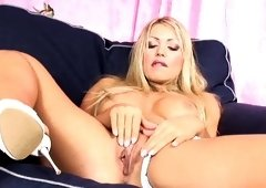 A sexy blonde with big tits is tweaking her hot clit with her hand