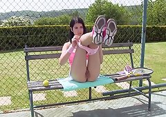 Cute tennis girl sits on a bench on the court to masturbate