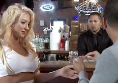 A blonde with large tits gets a dick in her mouth in a bar