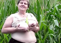 Fatty in a corn field fucks a veggie into her old pussy